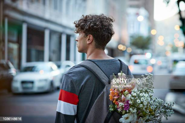 bike messenger carrying flowers in backpack - curly hair stock pictures, royalty-free photos & images