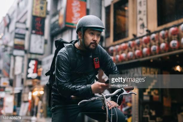 bike messenger checking for directions on a smartphone - homens de idade mediana imagens e fotografias de stock