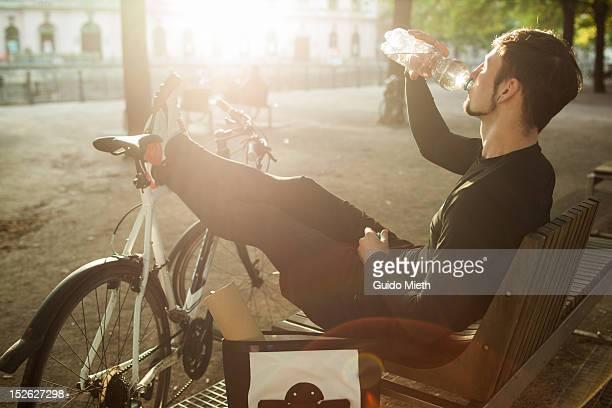 bike messenger drinking water - gegenlicht stock-fotos und bilder