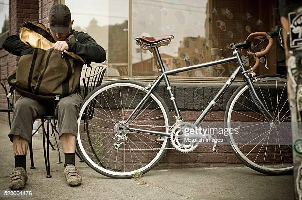 Bike messenger looking through bag