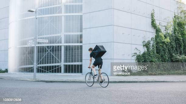 bike messenger riding down the street. - bicycle messenger stock pictures, royalty-free photos & images