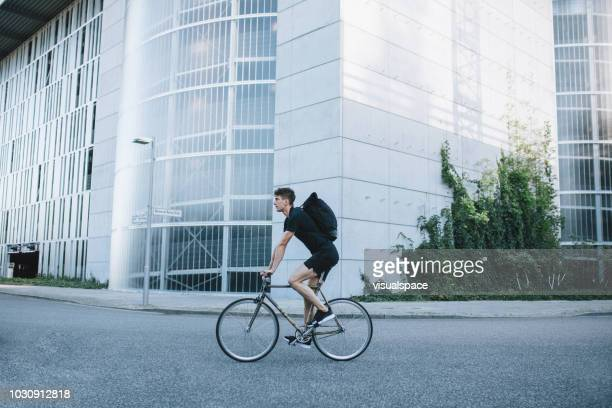 bike messenger riding down the street. - riding stock pictures, royalty-free photos & images