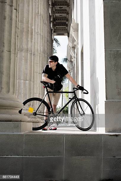Bike messenger taking break beside column