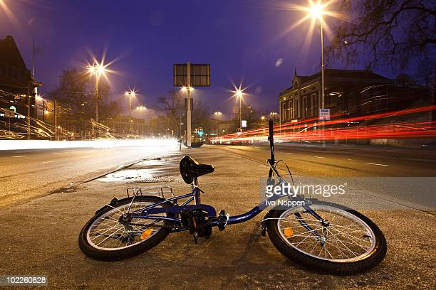 bike on pavement between two roads at night - arnhem stockfoto's en -beelden