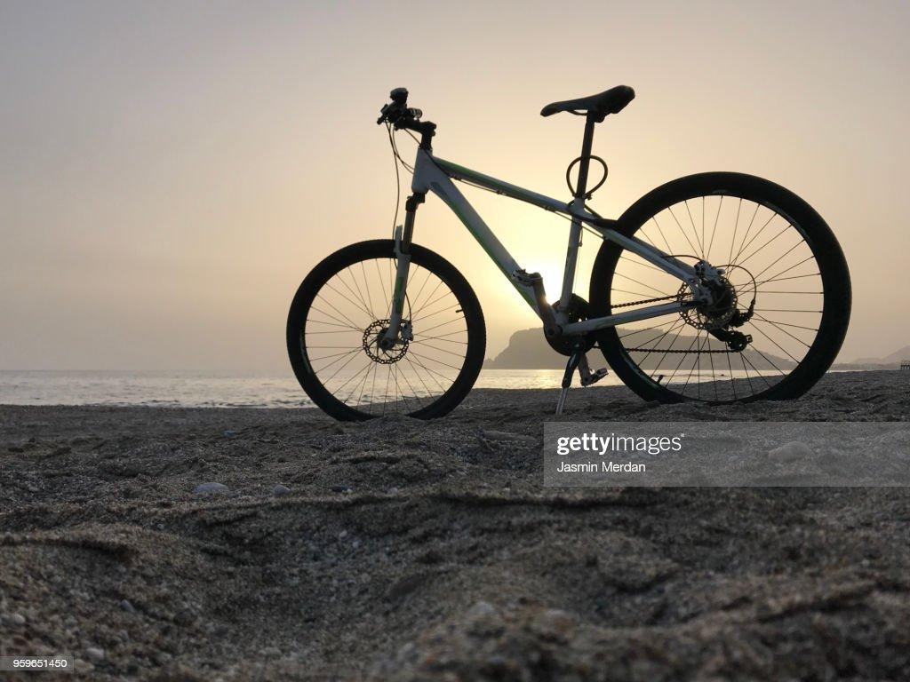 Bike on sunset beach : Stock-Foto