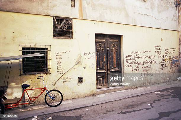 'Bike parked in front of graffiti covered wall, Cuba'