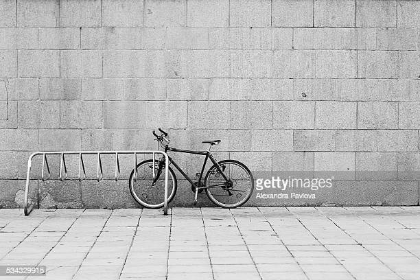 bike parked in the street next to rack and wall