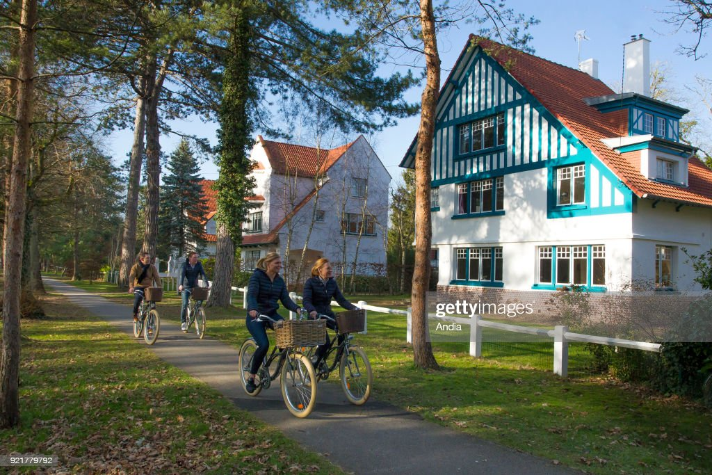 Bike ride in Le Touquet (northern France). Two couples riding bikes on a cycle lane and passing by typical houses from Le Touquet.