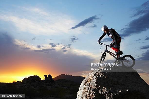 Bike rider balancing on rock boulder, side view