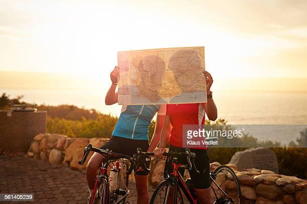 Bike riders looking at map, at sunset