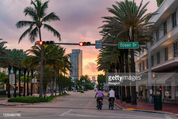 bike riders on ocean drive south beach miami during coronavirus pandemic - empty streets stock pictures, royalty-free photos & images