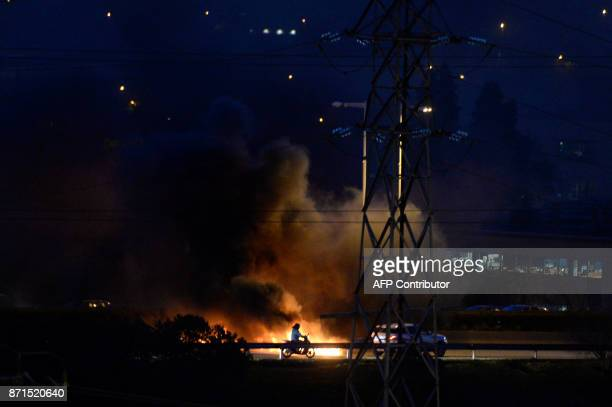 A bike rides past a fire burning at a picket on the Ronda de Dalt road in Barcelona during a general strike to protest the jailing of eight sacked...