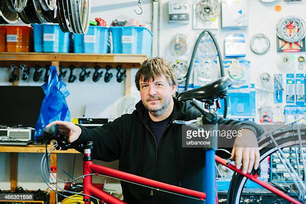 Bike shop and proprietor, portrait. Looking at the camera