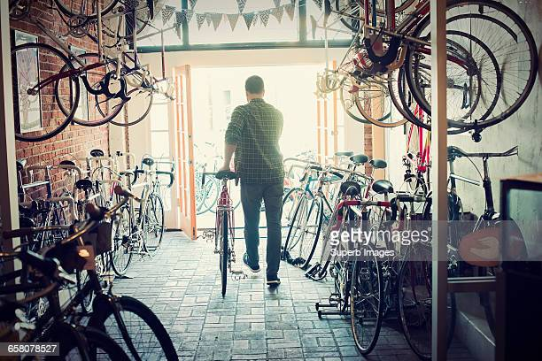 bike shop customer walks out with purchase - small business stock pictures, royalty-free photos & images