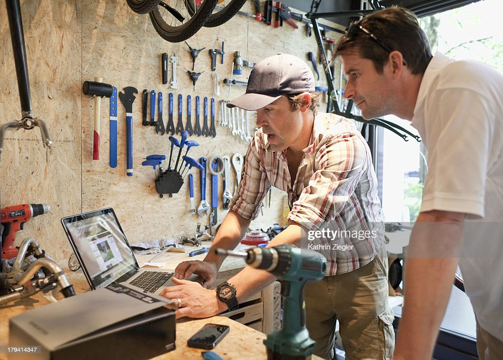 bike shop owner discussing products with client : Stock Photo