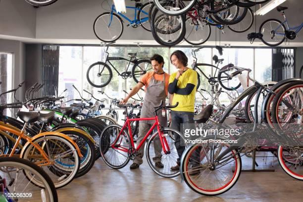 Bike shop owner helping customer choose bicycle