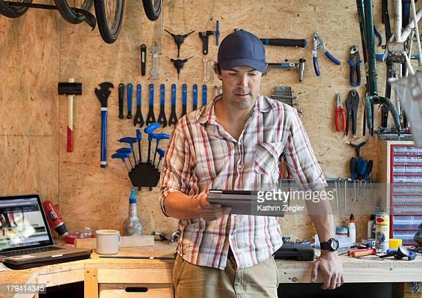 bike shop owner in workshop, using digital tablet