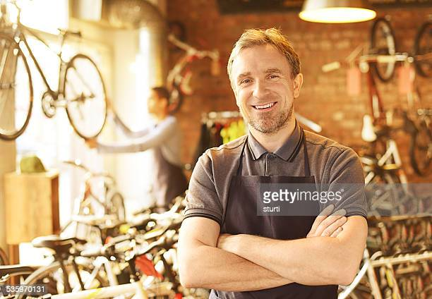 bike shop owner stands proudly in front of his stock
