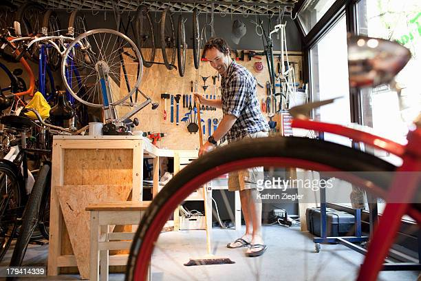 bike shop owner sweeping before opening workshop