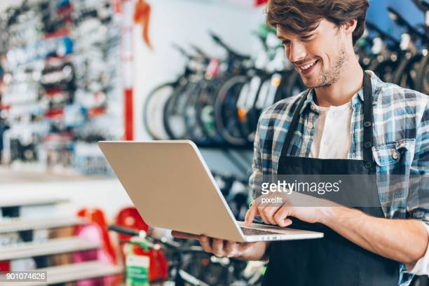 bike shop owner with laptop - net sports equipment stock pictures, royalty-free photos & images