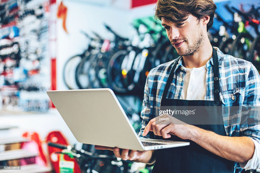 Bike shop owner working on a laptop : Stock Photo