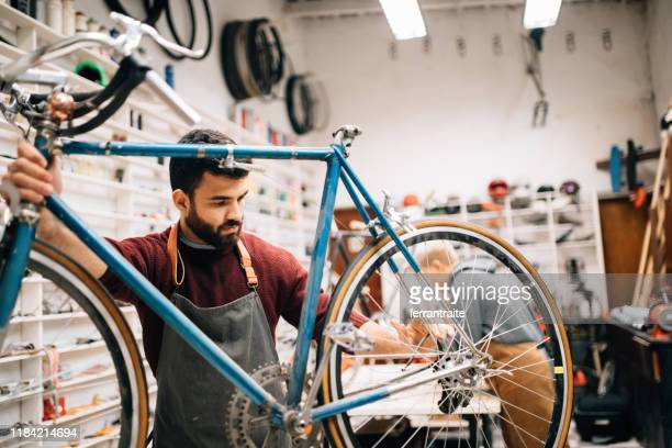 bike shop owner working on vintage bicycle - freelance foto e immagini stock