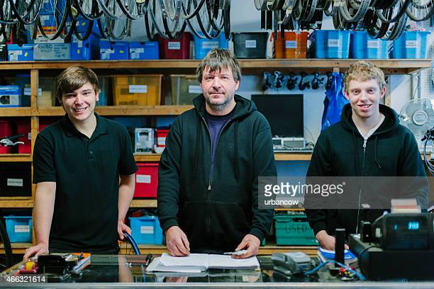 Bike shop proprietor and assistants, portrait. Looking at the camera