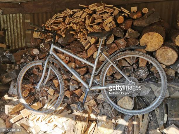 bike stored under a firewood canopy - charleroi stock pictures, royalty-free photos & images