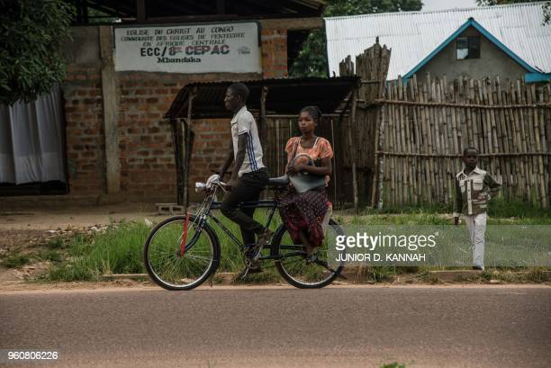 A bike taxi carries a woman past the Church of Christ during Pentecost celebrations on May 20 2018 in Mbandaka northwest of DR Congo as 45 cases of...