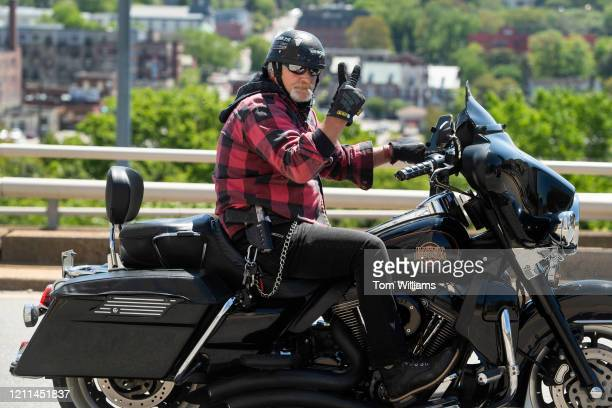 A biker armed with a Ruger handgun is seen near Capitol Square during a rally to demand that Gov Ralph Northam lift restrictions that have closed...