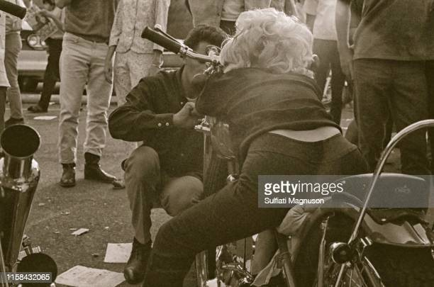 Biker chick in black, resting on her bike, seen from behind at the 1st Elysian Park Love-In on March 26, 1967 in Los Angeles, California.
