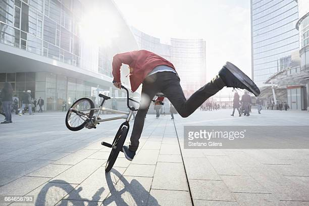 bmx biker doing stunt in urban area - bmx cycling stock pictures, royalty-free photos & images