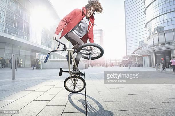 bmx biker doing stunt in urban area - truco fotografías e imágenes de stock