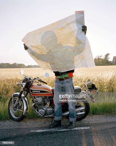 A biker holding a map in front of him.