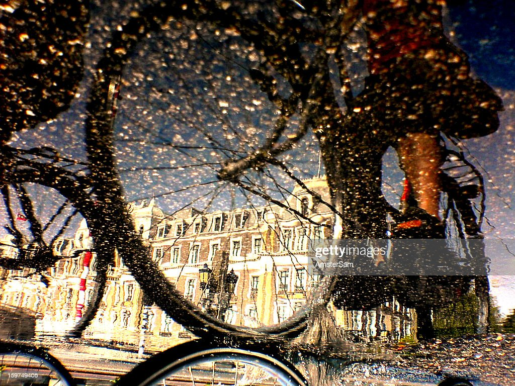 CONTENT] Biker in Amsterdam reflected in a puddle, some saturation and contrast added, no Photoshop.