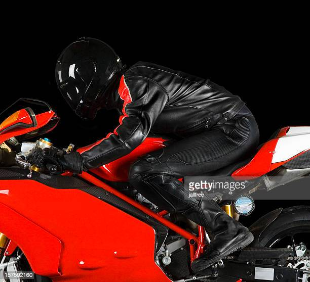 Biker in riding red superbike on black background