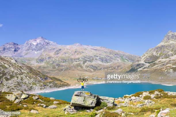 biker in triunph looking the mountain landscape from a rock with a mountain bike. - italia stockfoto's en -beelden
