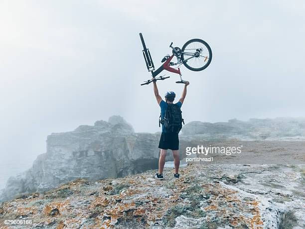 biker lifting up his bike on top of the cliff - extreme terrain stock pictures, royalty-free photos & images