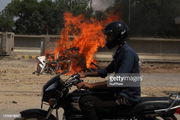 Biker moves past the burned chinese products during a protest against Chinese President Xi Jinping in Gurugram on the outskirts of New Delhi, India...