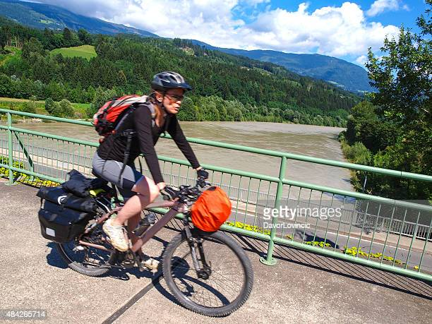 Biker on Drau cycle path over dam near Spittal, Austria