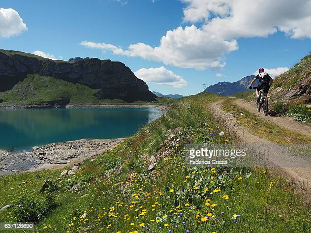 Biker On Mountain Road On The Shores Of Lake Toggia, Formazza Valley, Northern Italy