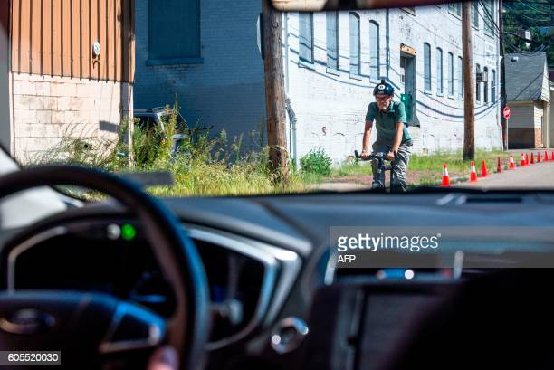 A biker passes a pilot model of the Uber selfdriving car on September 13 2016 in Pittsburgh Pennsylvania Uber launched a groundbreaking driverless...