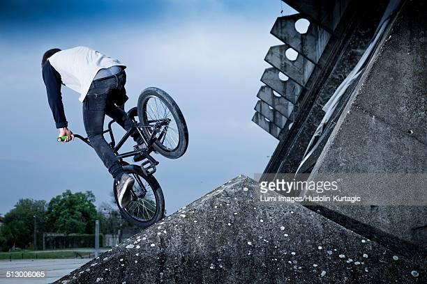 BMX biker performing a stunt on a bridge