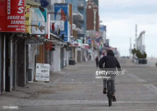 A biker rides along the empty boardwalk on April 27 2020 in Ocean City Maryland The beach and boardwalk were closed after Maryland Governor Larry...