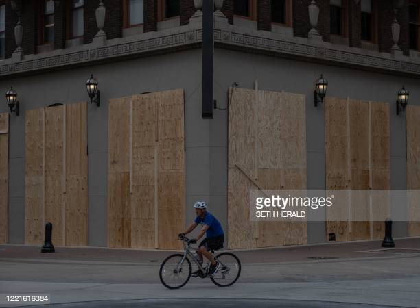 A biker rides past a boarded up building ahead of US President Donald Trump's campaign rally in Tulsa Oklahoma June 202020 Hundreds of supporters...