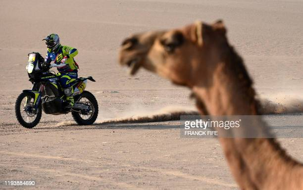 Biker rides past a camel as he competes during the Stage 10 of the Dakar 2020 between Haradh and Shubaytah, Saudi Arabia, on January 15, 2020.