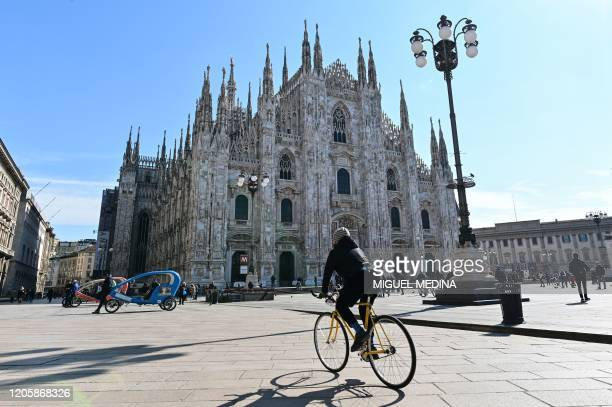 A biker rides past the Duomo di Milano on Piazza del Duomo in central Milan on March 8 after millions of people were placed under forced quarantine...