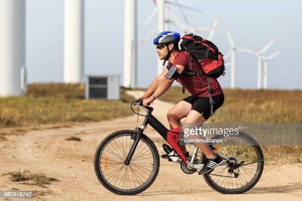 Biker riding in front of wind turbine farm