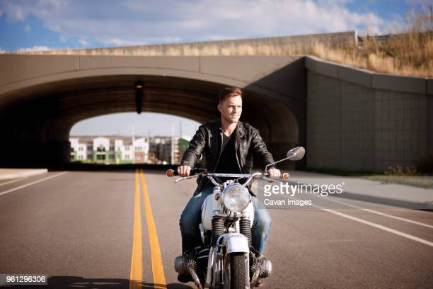 Biker riding motorcycle with bridge in background
