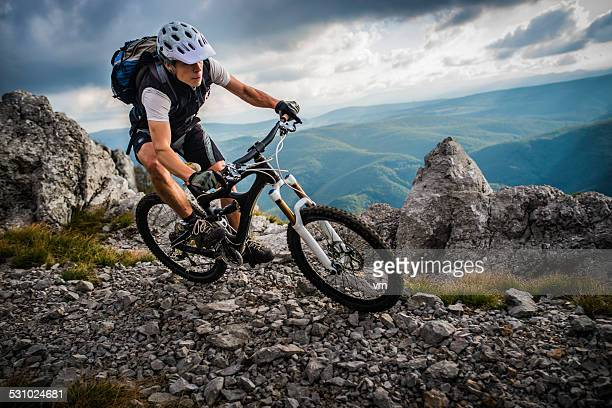 biker riding on a mountain trail - buitensport stockfoto's en -beelden